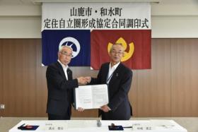 中嶋山鹿市長と高巣和水町長が協定を結んでいる写真