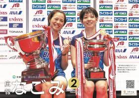 第74回全日本総合バドミントン選手権大会の女子ダブルスで優勝した福島由紀選手と廣田彩花選手が、優勝カップと金メダルを手に持って微笑んでいる写真